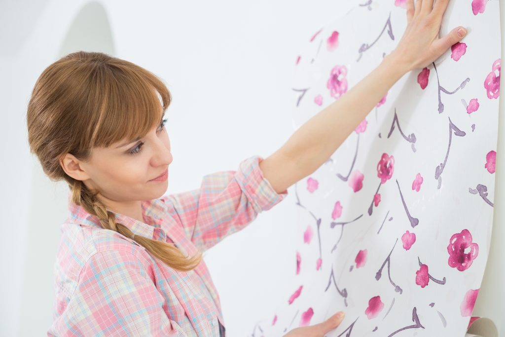 Woman Putting Wallpaper in Home