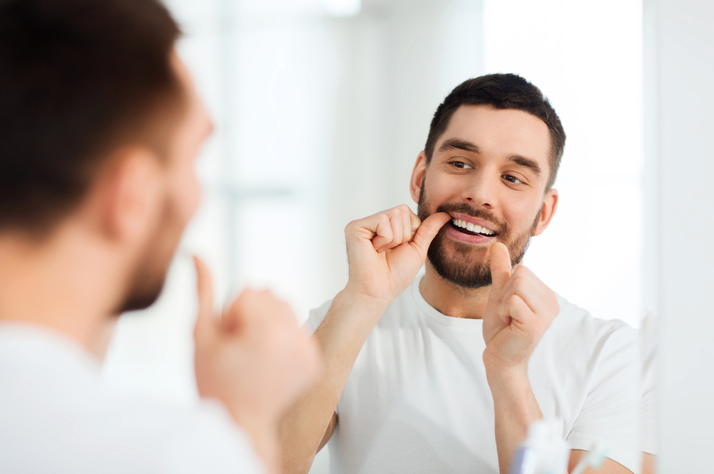 man flosses while looking in mirror