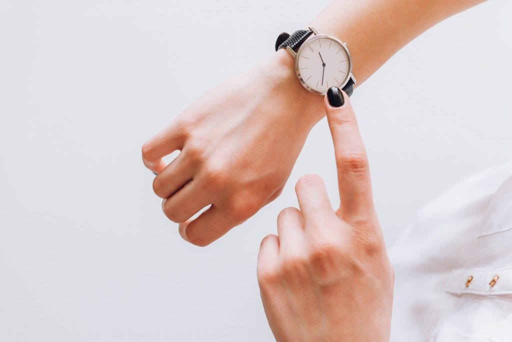 woman looking at her watch, signs your husband is cheating