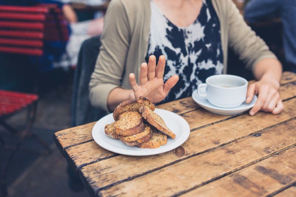 Woman pushing away bread plate