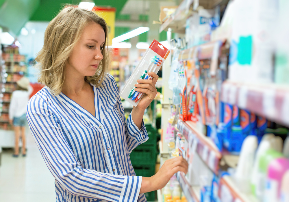 woman buys new toothbrush at store
