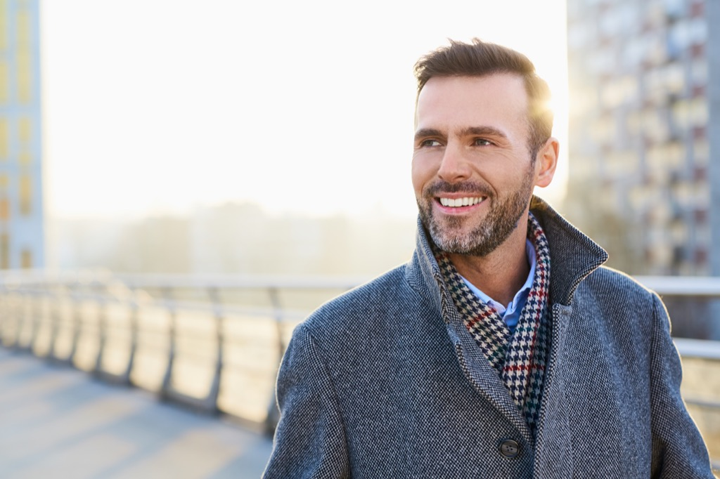 middle aged man walking on a bridge and smiling, how to make friends as an adult