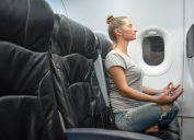 young woman sits in jeans and a gray T-shirt in a black armchair plane. sits in a yoga posture and feels calm