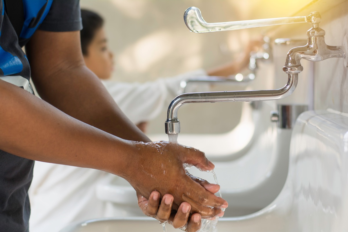 Man and little boy washing hands at sink