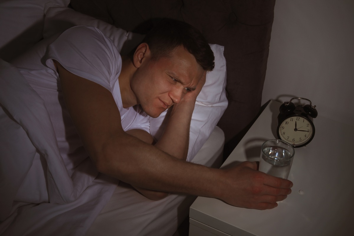 30-something white man reaching for glass of water in bed