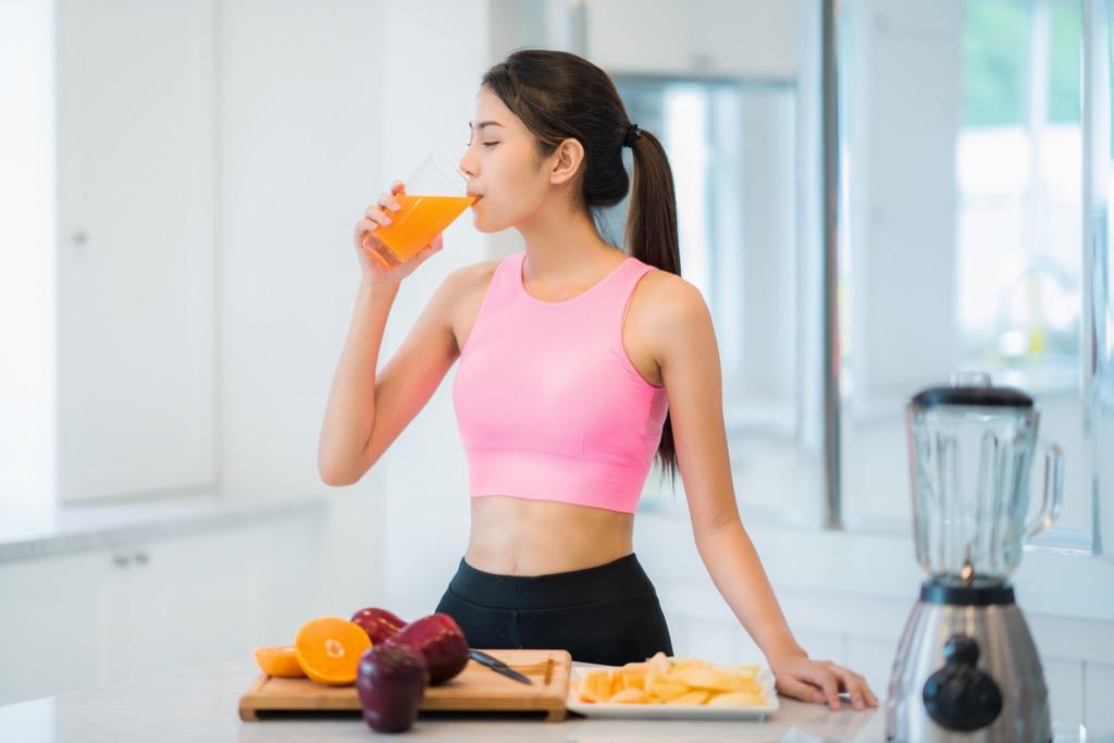 woman drinking orange juice, stomach symptoms