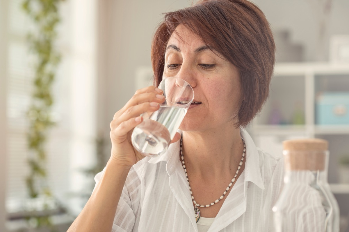 Older woman drinking a glass of water