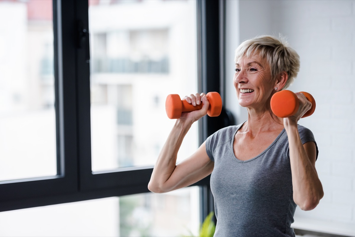Older woman lifting weights and working out at the gym