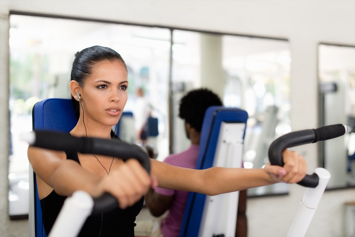 Younger woman working out on a machine at the gym