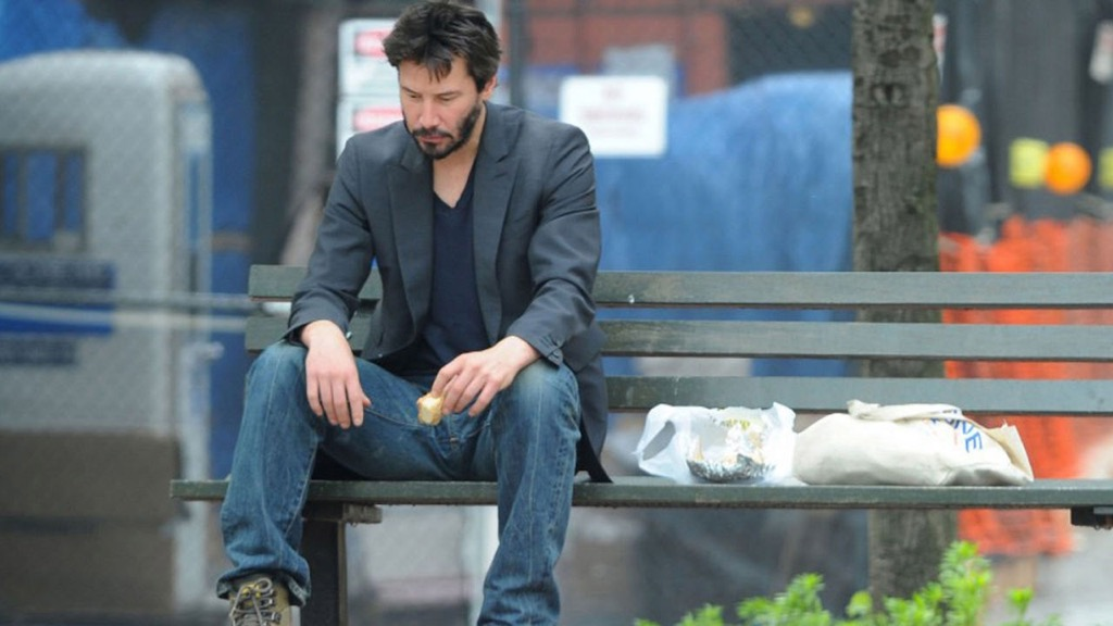 Sad Keanu sitting on a bench