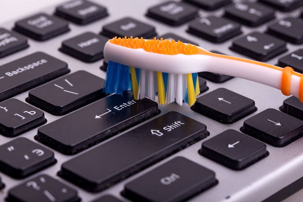 Person Cleaning a Keyboard with a Toothbrush Cleaning Hacks