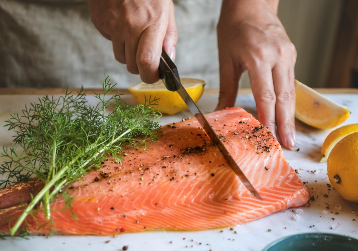 Person preparing a filet of salmon
