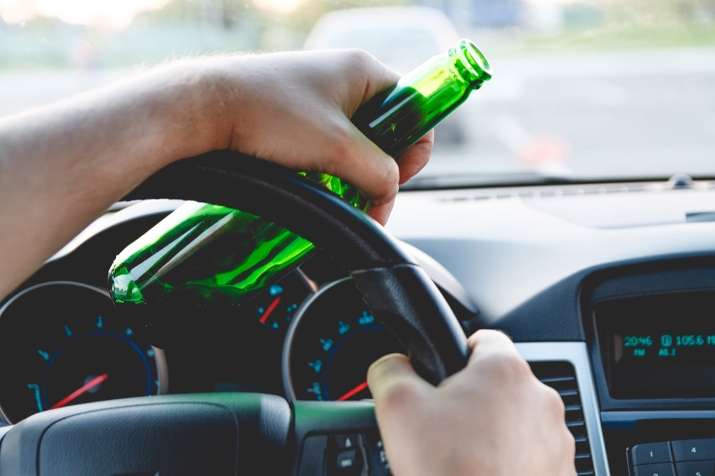 drunk driver holding beer bottle about to get dui
