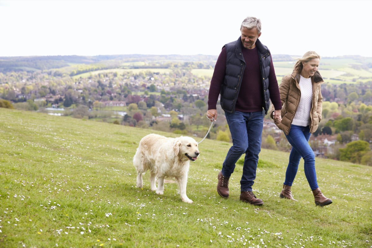 middle age couple walking their dog