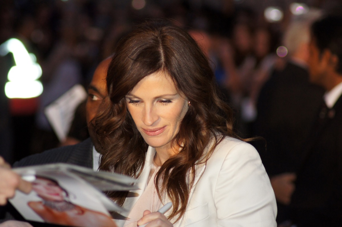 Julia Roberts signing an autograph on red carpet