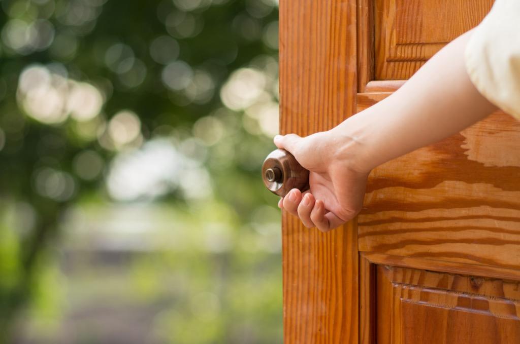 opening door with hand on doorknob