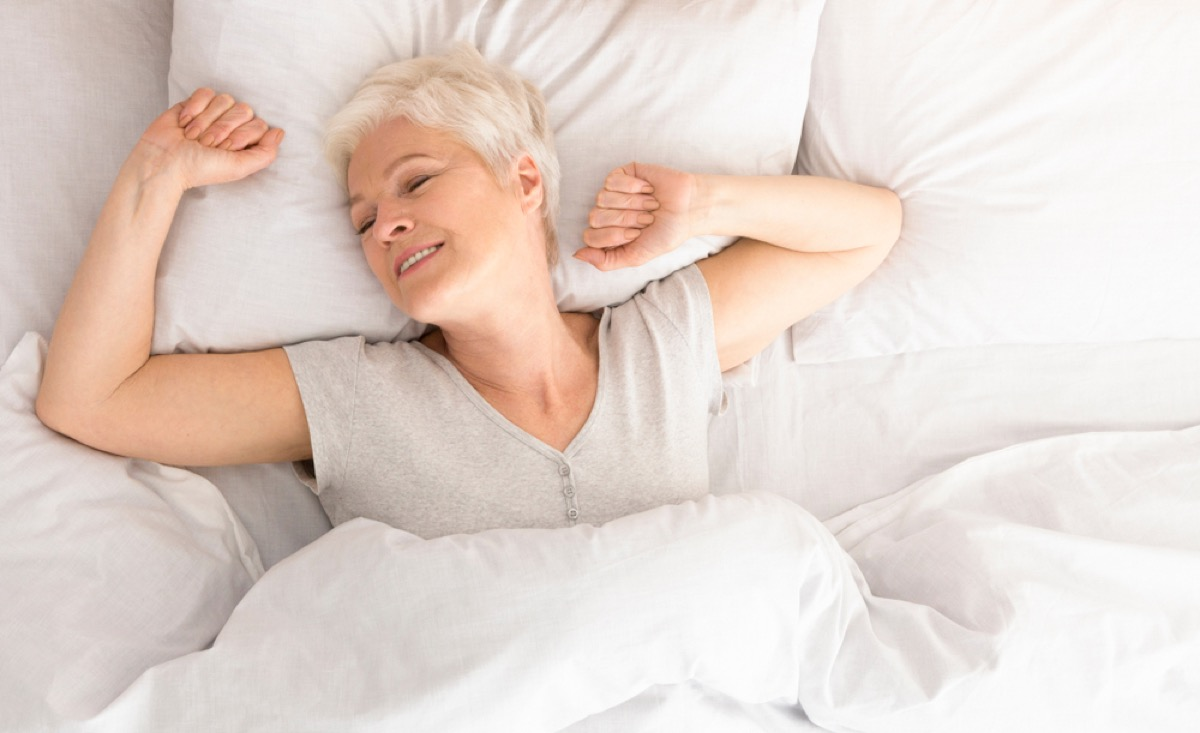 senior white woman stretches in bed as she wakes up