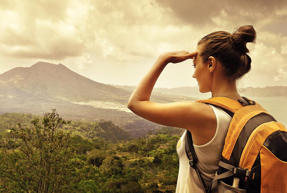 solo female traveler surveys her lush surroundings