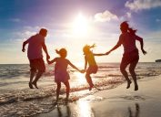 Shadowy photo of family of four jumping in ocean, things that annoy grandparents