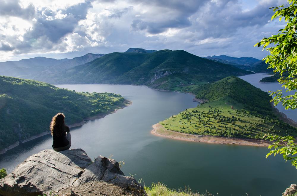 woman sitting alone on mountain