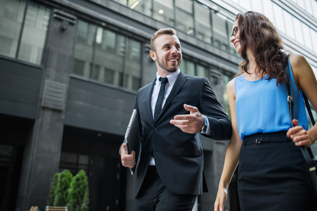 a man and a woman in business suits walk and talk Science-Based Happiness Hacks