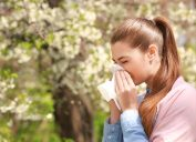 Girl sneezing outside by tree
