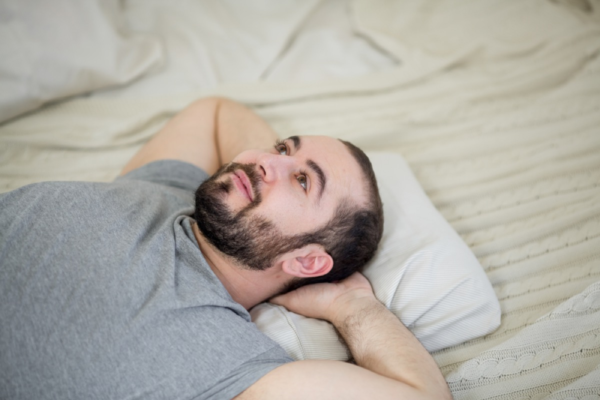 young white man on bed with eyes open