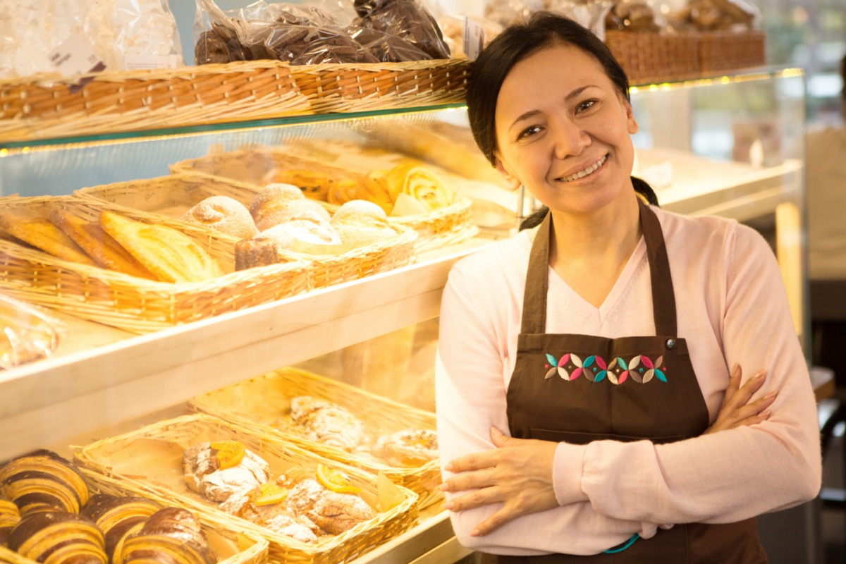 middle age asian woman standing in front of her pastries
