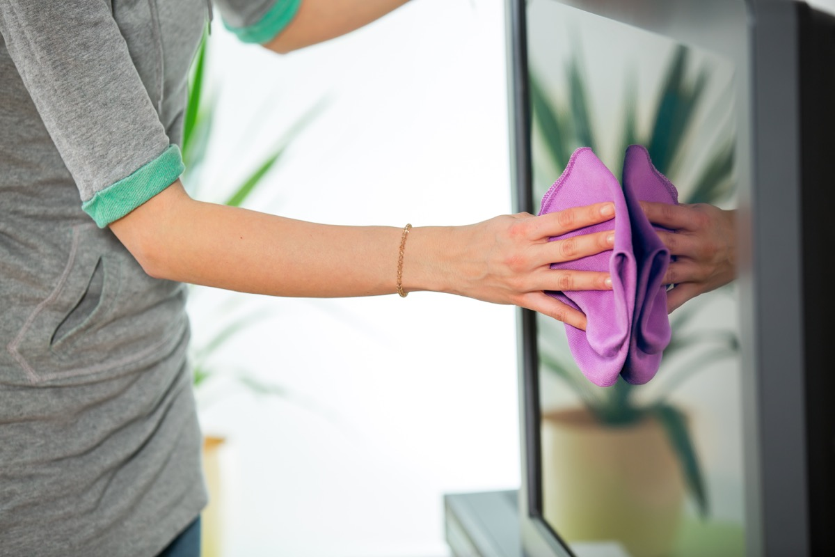 Woman Cleaning a TV Screen With a Cloth Cleaning Hacks