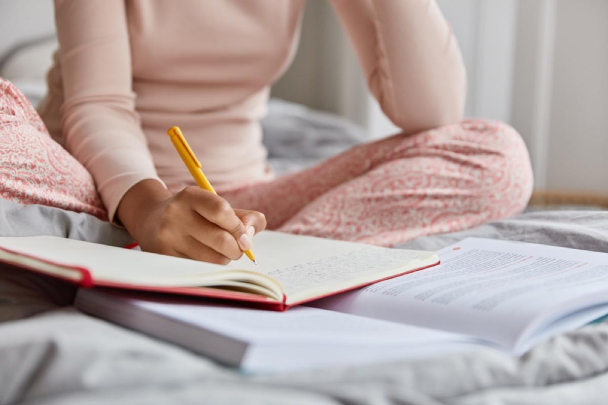 woman journaling in bed before sleep
