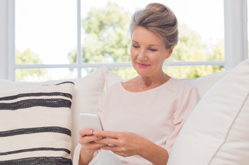 Older woman on smartphone things grandparents should never do