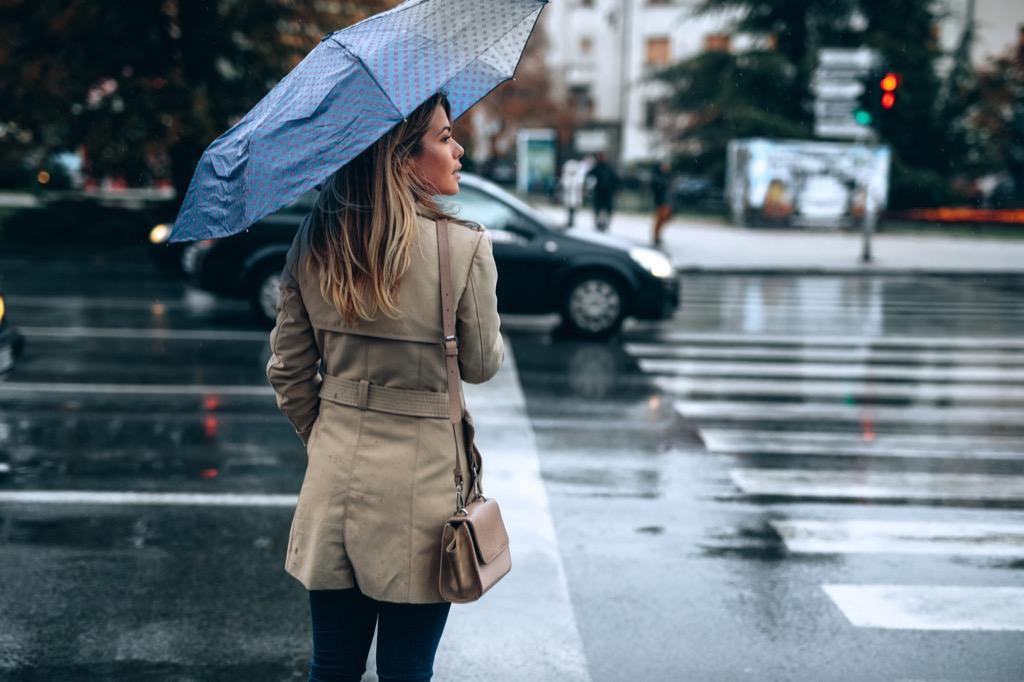 Woman crossing street with umbrella