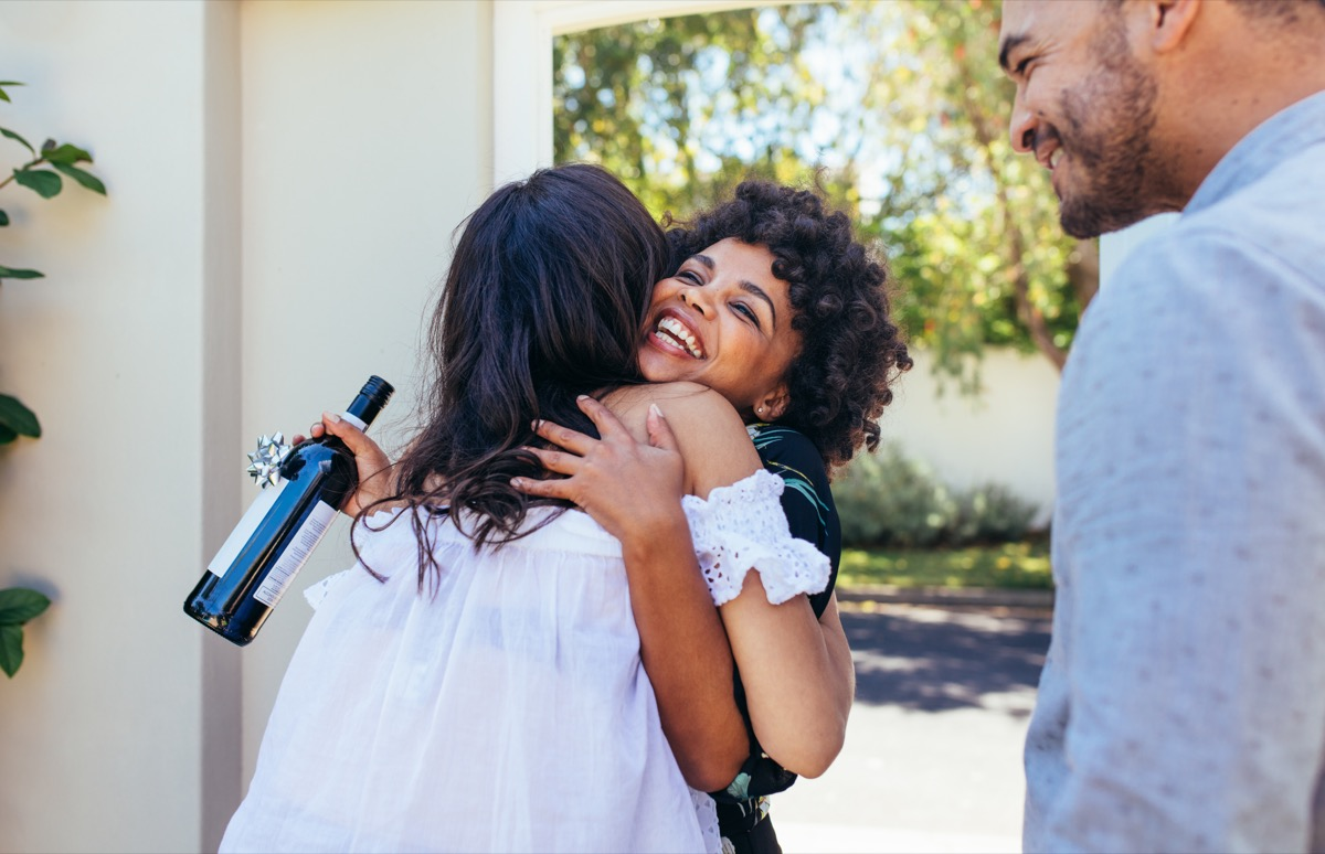 Black woman with natural hair hugs female friend at door with housewarming wine in hand, worst things about the suburbs