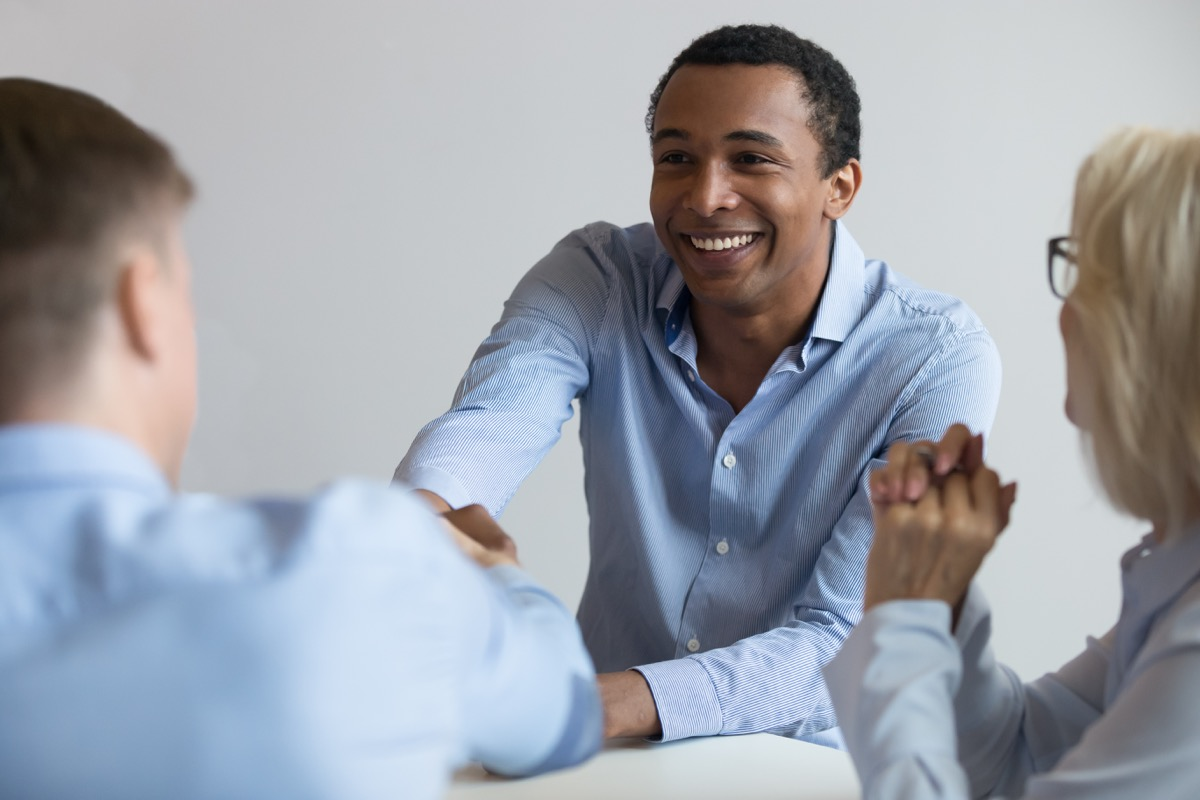 Black 40-something year-old man shakes hand of white male interview sitting across the table, etiquette over 40