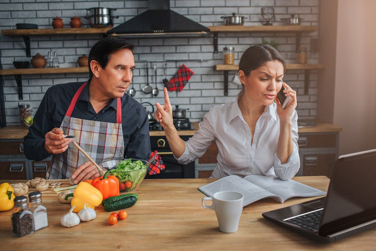 Latino man wearing apron interrupts wife on phone call in the kitchen, etiquette over 40