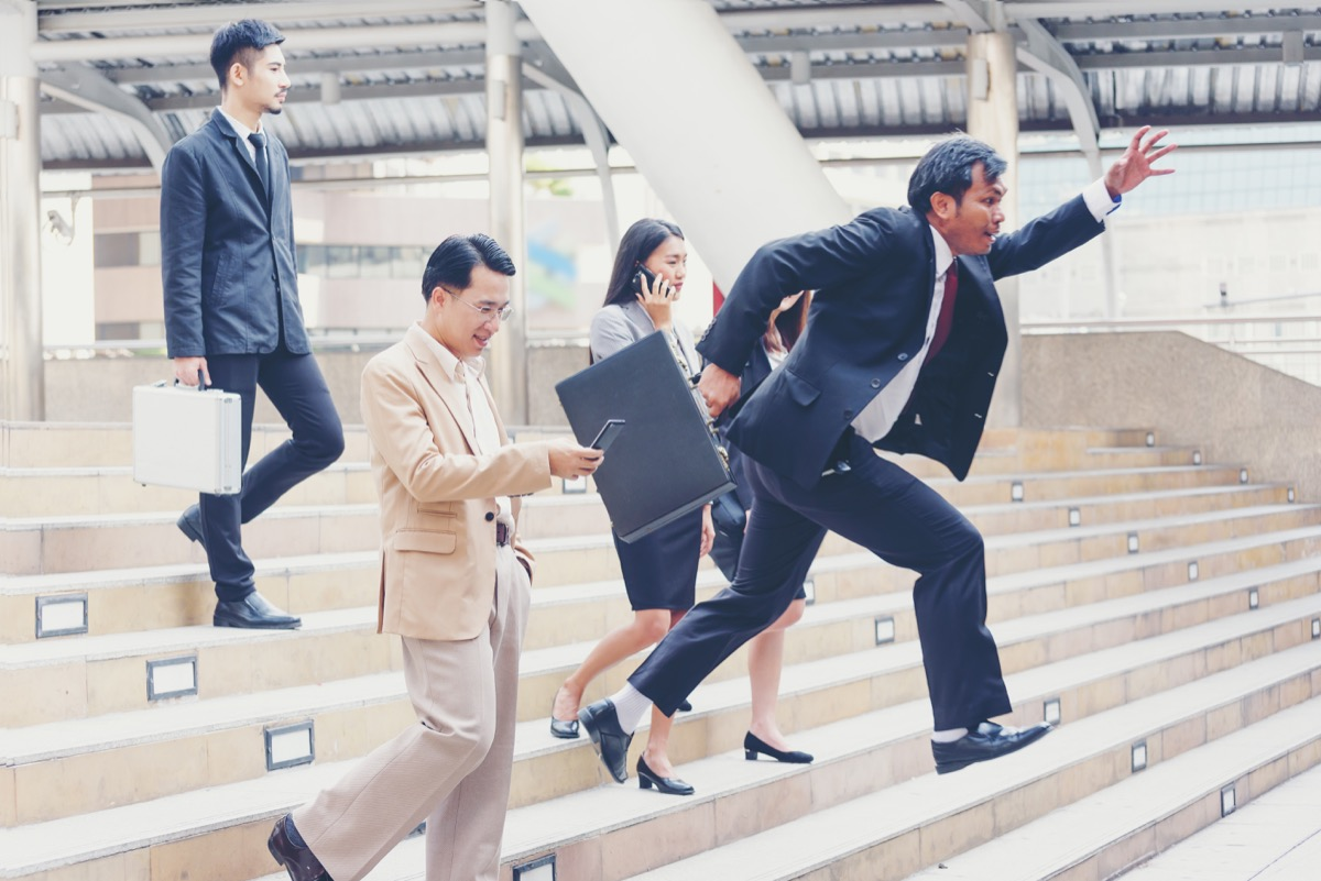Asian businessman races down steps, passing three other business people, etiquette over 40
