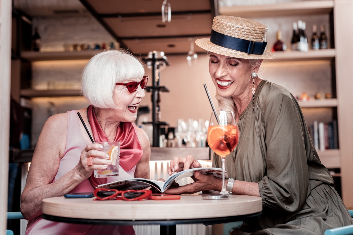 Two older women have drinks and read book together, one wears a hat indoors, long marriage tips
