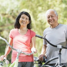 Mature Asian couple (60s) in the park, riding bicycles.