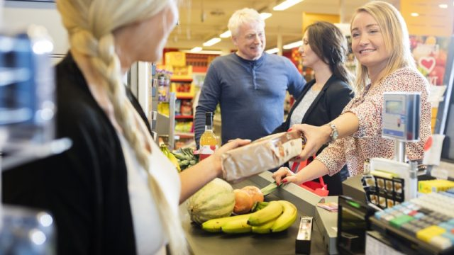woman checking out at grocery store, worst things about the suburbs