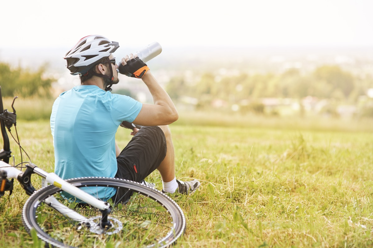 Man drinking from a water bottle with his bike