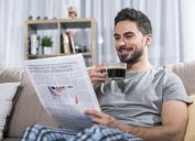 man laughing at newspaper