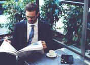 man newspaper cafe waiting