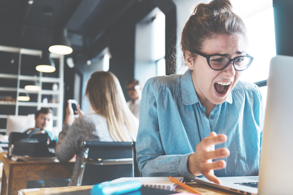 stressed out woman screams at computer, working mom