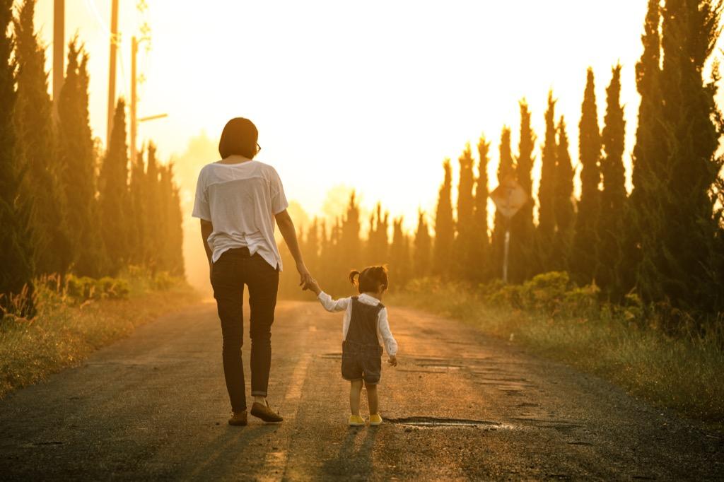 mother daughter walking trees
