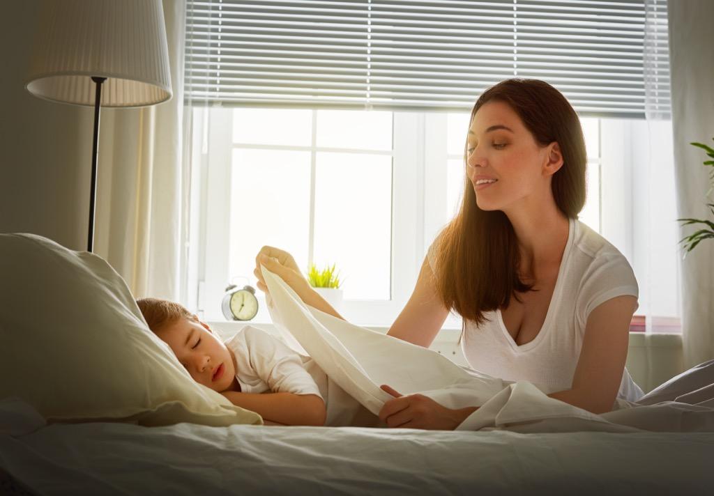 mother tucking daughter sleep