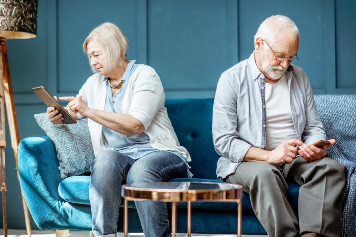 older couple ignoring each other on couch using smartphone and tablet, over 50 regrets