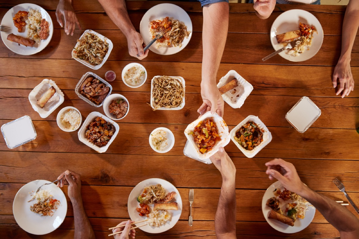 people reaching across table for food, etiquette mistakes