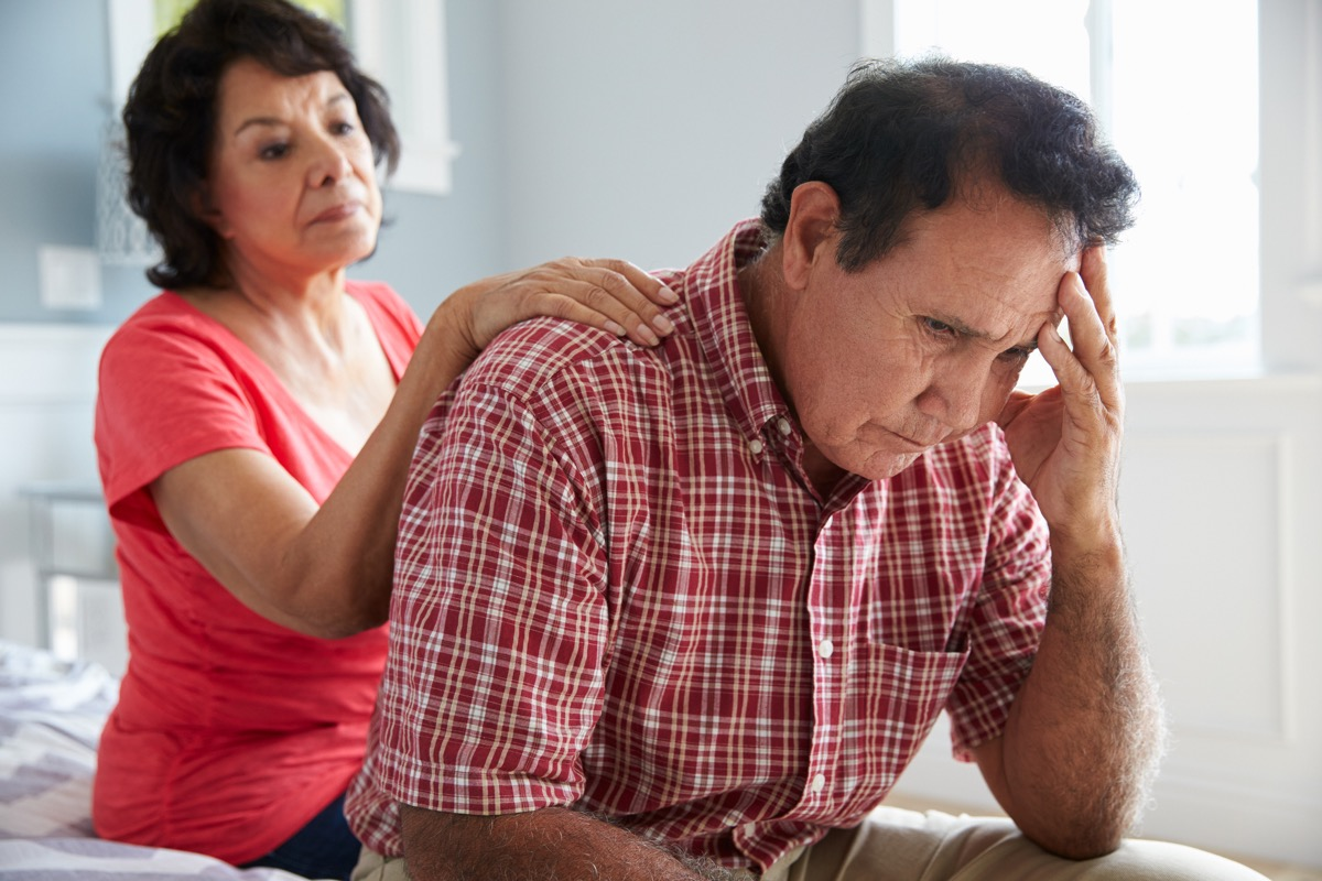 Wife Comforting Senior Husband Suffering With Dementia and looking confused