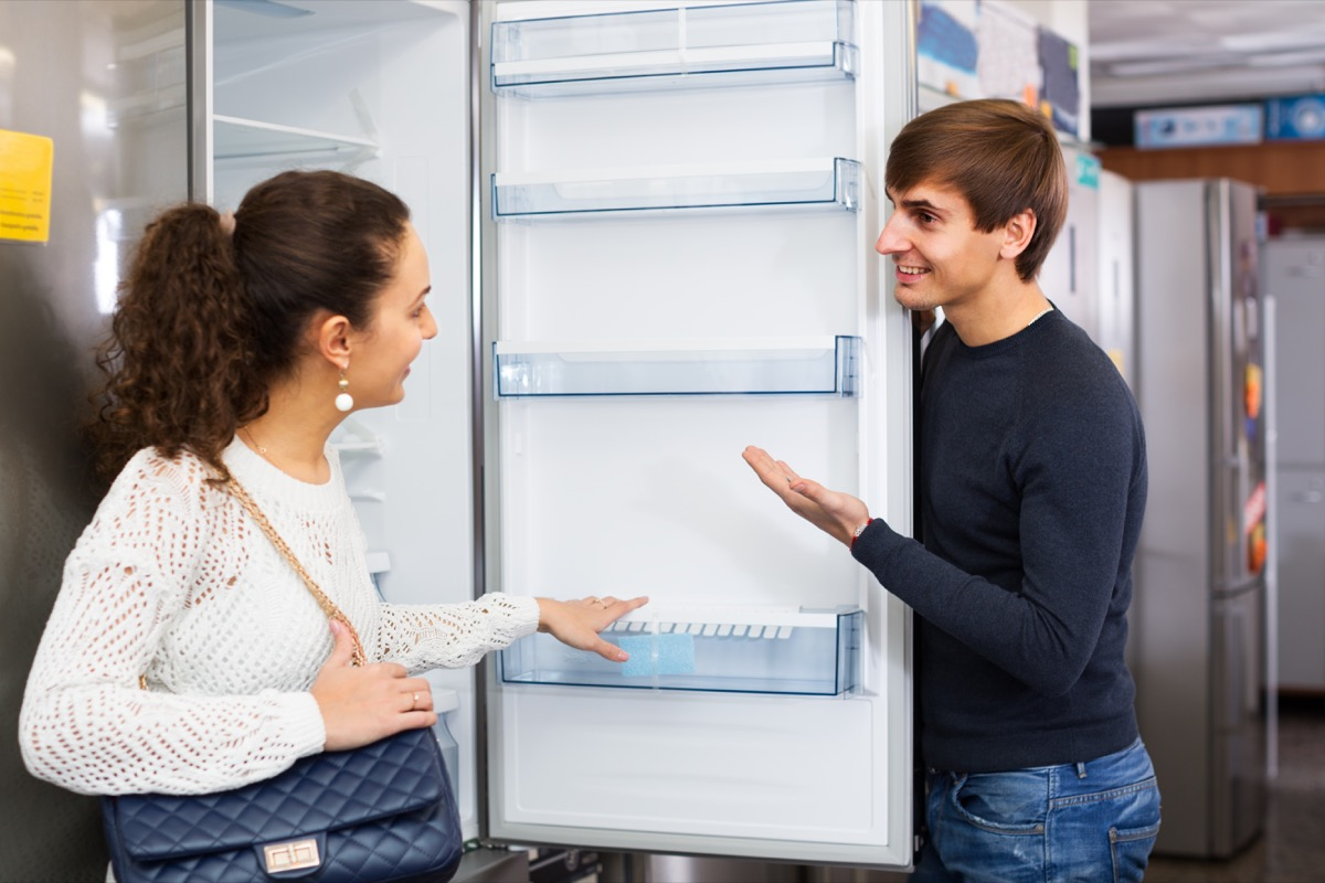 Two people shopping for a new refrigerator