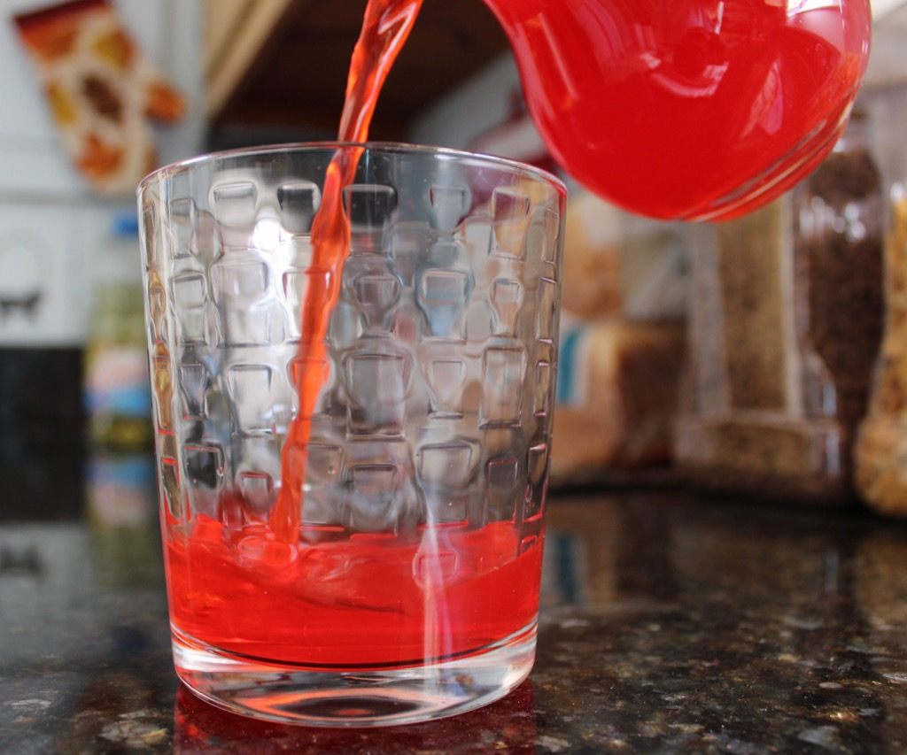 red drink is poured from pitcher into tumbler glass, fact about nebraska